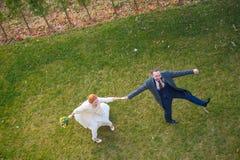 Braut und Bräutigam, die auf das Händchenhalten des grünen Grases gehen Stockfotografie