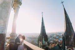 Braut und Bräutigam, die auf dem Balkon der alten gotischen Kathedrale sich halten Stockfoto