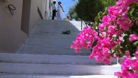 Braut und Bräutigam, die auf der Treppe auf der Straße stehen Glückliche Paare in der Weinlesekleidung photosession der Jungvermä stock footage