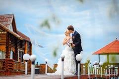 Braut und Bräutigam, die auf einer Brücke an ihrem Hochzeitstag küssen Lizenzfreie Stockbilder
