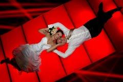 Braut und Bräutigam, die auf rotem Boden liegen Lizenzfreie Stockfotografie