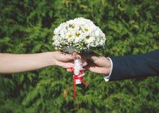 Braut und Bräutigam, die Brautblumenstrauß halten Lizenzfreies Stockfoto