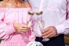 Braut und Bräutigam, die Champagnergläser und Brautblumenstrauß halten Lizenzfreie Stockfotografie
