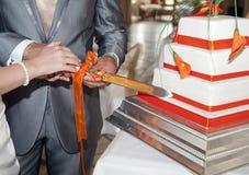 Braut und Bräutigam, die den Kuchen schneiden Lizenzfreie Stockbilder