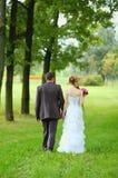 Braut und Bräutigam, die in den Park gehen Stockbild