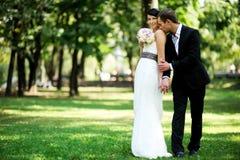 Braut und Bräutigam, die draußen auf Hochzeitstag aufwerfen Lizenzfreies Stockbild