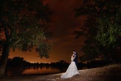 Braut und Bräutigam, die durch den See unter den Sternen umfassen Lizenzfreie Stockfotos
