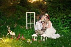 Braut und Bräutigam, die in einem Park auf dem Gras sitzen Lizenzfreie Stockbilder