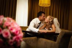 Braut und Bräutigam, die in einem stilvollen Aufenthaltsraum sitzen stockbilder