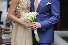 Braut und Bräutigam, die einen Hochzeitsblumenstrauß von Callas halten lizenzfreies stockfoto