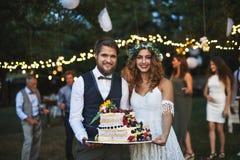 Braut und Bräutigam, die einen Kuchen am Hochzeitsempfang draußen im Hinterhof halten stockbild