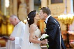 Braut und Bräutigam, die in einer Kirche küssen Lizenzfreie Stockfotografie