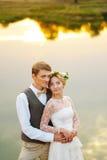 Braut und Bräutigam, die gegen einen See umarmen Das Wasser reflektiert die Wolken Lizenzfreies Stockbild