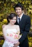 Braut und Bräutigam, die Hand und Weg im Garten halten Stockbild