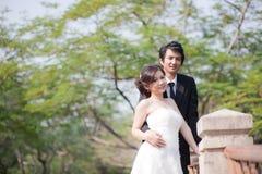 Braut und Bräutigam, die Hand und Weg im Garten halten Lizenzfreie Stockbilder