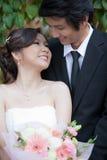 Braut und Bräutigam, die Hand und Weg im Garten halten Stockbilder