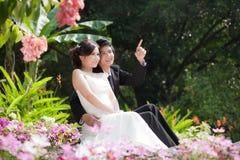 Braut und Bräutigam, die Hand und Weg im Garten halten Lizenzfreies Stockbild