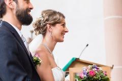 Braut und Bräutigam, die Hochzeit in der Kirche am Altar haben Lizenzfreie Stockfotos