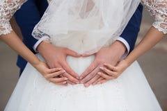 Braut und Bräutigam, die ihre Hände in einer Herzform halten Stockfotografie