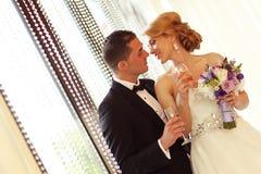 Braut und Bräutigam, die an ihrem Hochzeitstag rösten Lizenzfreies Stockfoto
