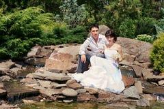 Braut und Bräutigam, die im Garten aufwerfen stockfoto