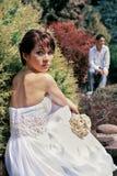 Braut und Bräutigam, die im Garten aufwerfen lizenzfreie stockfotografie