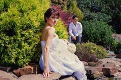Braut und Bräutigam, die im Garten aufwerfen stockfotografie
