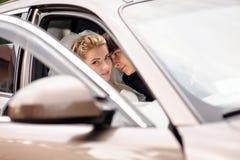 Braut und Bräutigam, die im Hochzeitsauto küssen Lizenzfreie Stockfotografie