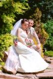Braut und Bräutigam, die im Park aufwerfen lizenzfreie stockfotografie