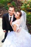 Braut und Bräutigam, die im Park aufwerfen stockfotos