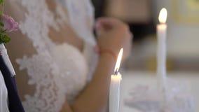 Braut und Bräutigam, die Kerzen in der Kirche an der Zeremonie halten stock video