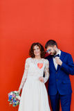 Braut und Bräutigam, die nahe bei einer roten Wand stehen Stockfotografie