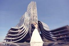 Braut und Bräutigam, die nahe metallischem Bau küssen Stockfotografie