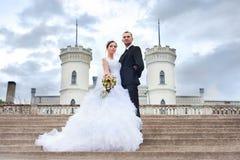 Braut und Bräutigam, die nahe Schloss aufwerfen lizenzfreie stockfotos