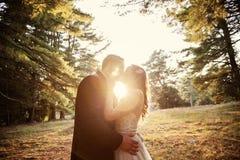 Braut und Bräutigam, die am Sonnenuntergang küssen Lizenzfreie Stockfotos