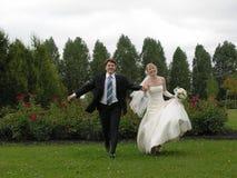 Braut und Bräutigam, die von den Bäumen laufen Lizenzfreies Stockfoto