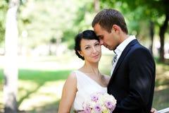 Braut und Bräutigam, die zusammen in einem Park stehen Stockfotografie
