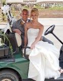 Braut und Bräutigam in einem Golfwagen Stockbild