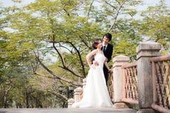 Braut und Bräutigam Embrace und Schauen im Garten Stockfoto