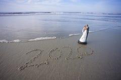 Braut und Bräutigam Figurine am Strand mit dem Jahr 2020 geschrieben in den Sand Stockbilder