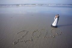 Braut und Bräutigam Figurine am Strand mit dem Jahr 2020 geschrieben in den Sand Lizenzfreie Stockbilder