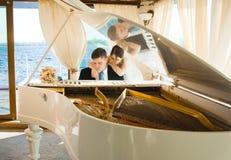 Braut und Bräutigam am großartigen Klavier Stockbild