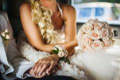 Braut-und Bräutigam-Händchenhalten im Auto lizenzfreie stockfotos