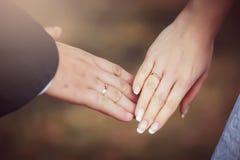 Braut-und Bräutigam-Hände mit Hochzeits-Ringen Stockfoto