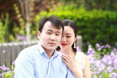 Braut und Bräutigam im Hochzeitskleid mit eleganter Frisur, wenn das weiße Hochzeitskleid auf der Bank sitzt, nahe bei dem Zaun Stockfotografie