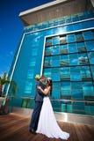 Braut und Bräutigam küßt nahe dem Gebäude Lizenzfreie Stockfotos