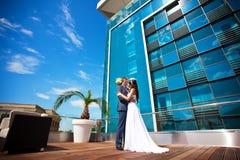 Braut und Bräutigam küßt nahe dem Glasgebäude Stockfotos