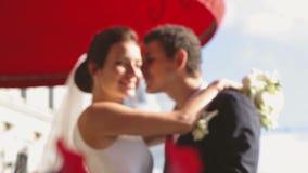Braut und Bräutigam küssen an der Straße nahe dem Hotel stock footage