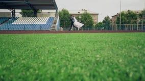 Braut und Bräutigam laufen entlang die Tretmühle am Stadion, das grüne Gras stock footage
