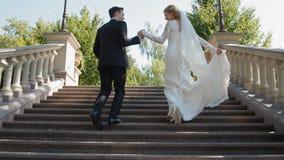 Braut und Bräutigam laufen herauf die Steintreppe stock video footage